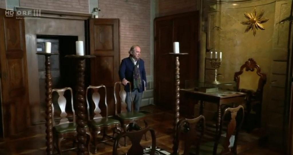 Mann in Saal mit Kerzenleuchtern und Stühlen